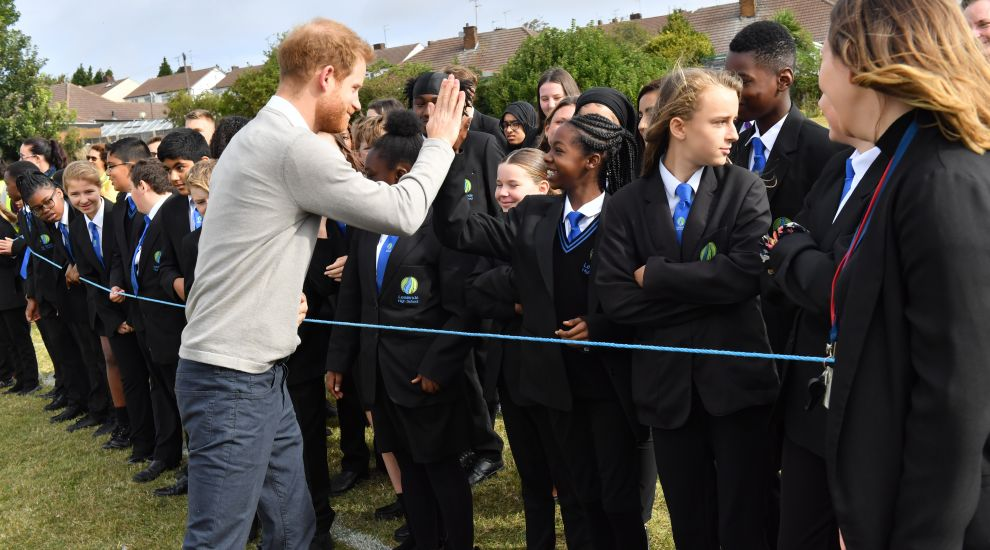 Harry high-fives and hugs pupils as he sees rugby scheme in action